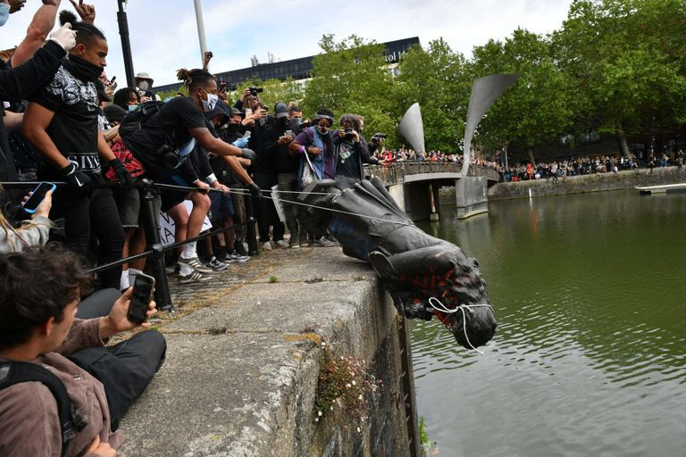Protesters in Europe attempt to throw a statue into an urban body of water.