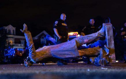 Two police officers stand behind a toppled confederate statue.
