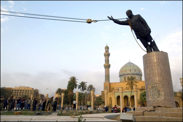 A statue of Saddam Hussein being toppled using ropes.