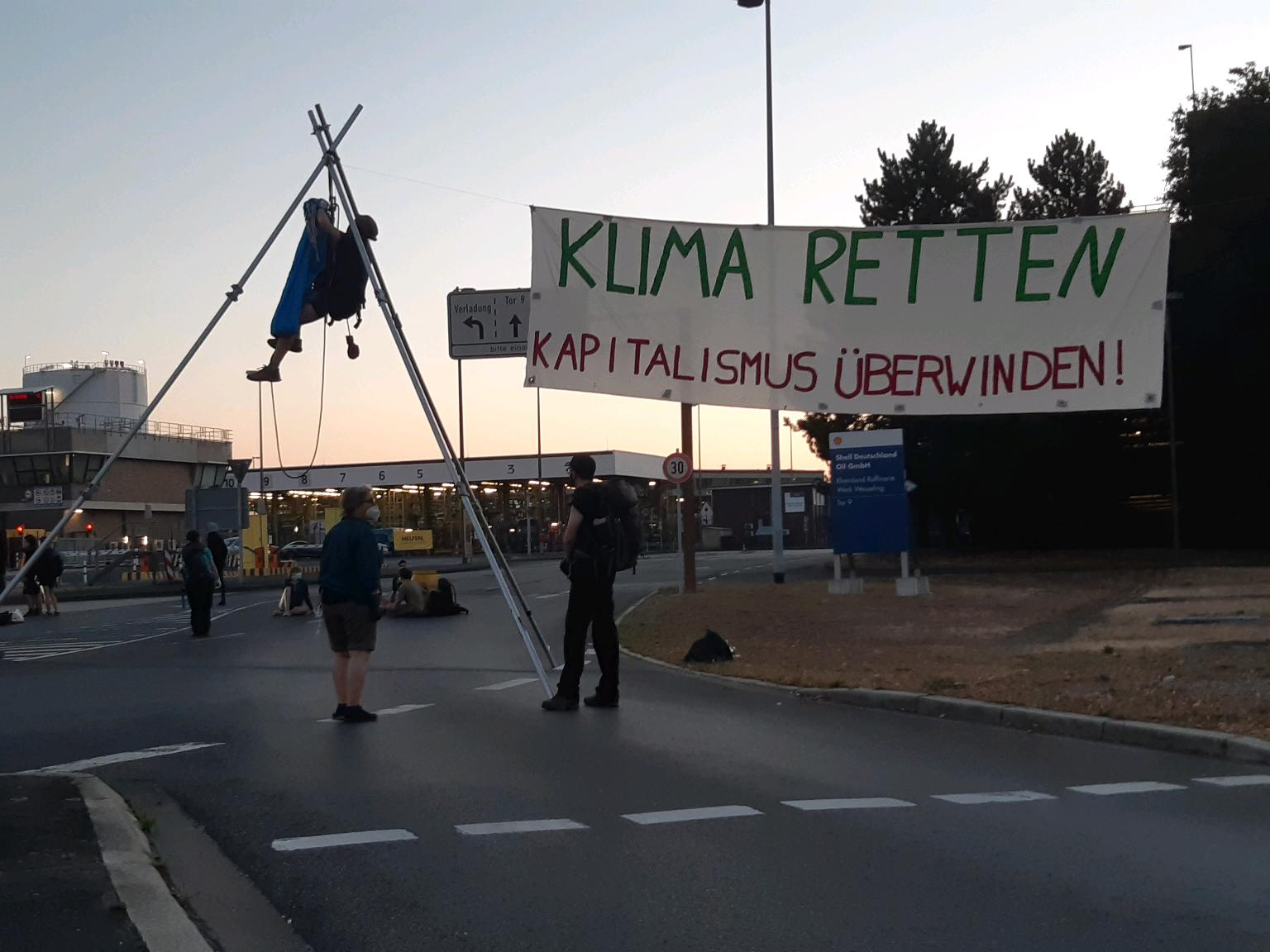 """Activists with """"SAVE THE CLIMATE OVERCOME CAPITALISM"""" banner at Gate 9 of the Shell refinery in Wesseling, Germany."""